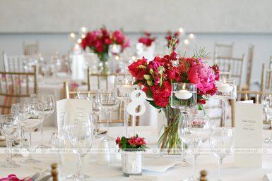 Bukiety malinowych kwiatów w dekoracji sali w Remesie