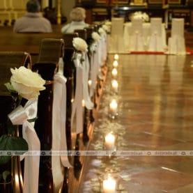 Subtelna biel róż w blasku świec – delikatny wystrój ślubny kościoła