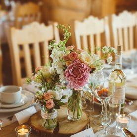 Kwiaty na plastrach drewna – dekoracja ślubna w Karczmie na Lednicy