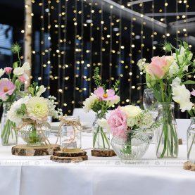 Dekoracja stołu prezydialnego – słoiczki, plastry drewna, kwiaty, świece – Hotel Barczyzna w Nekli