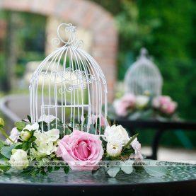 Dekoracja stołów na tarasie – białe klatki z kwiatami – Dworek Fantazja