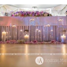 Świece, szkło, kwiaty – dekoracja przed stołem prezydialnym
