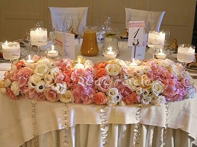 Pastelowe kwiaty w oprawie z koronki – dekoracja stołu pary młodej